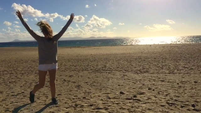 beautiful young girl with long hair playing with the windy day in the beach with slow motion with his hair dancing against the sunlight with nice smile and raising arms in a happy mood during a travel in the lanzarote island. - 東ヨーロッパ民族点の映像素材/bロール