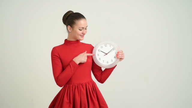 beautiful young girl with the clock shows the copy space on a gray background - hair bun stock videos & royalty-free footage