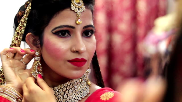 Beautiful young Indian bride looking in mirror