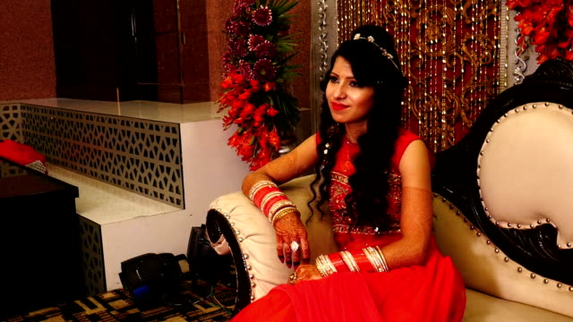 beautiful young indian bride sitting on luxury sofa in wedding reception hall - bride stock videos & royalty-free footage