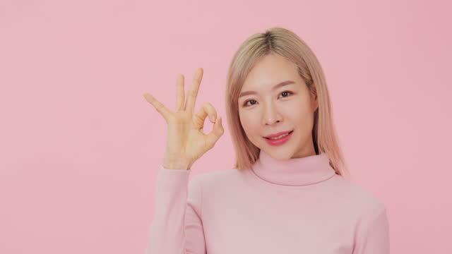 schöne junge koreanische mädchen zeigt ok geste, isoliert auf rosa hintergrund. - kosmetik stock-videos und b-roll-filmmaterial