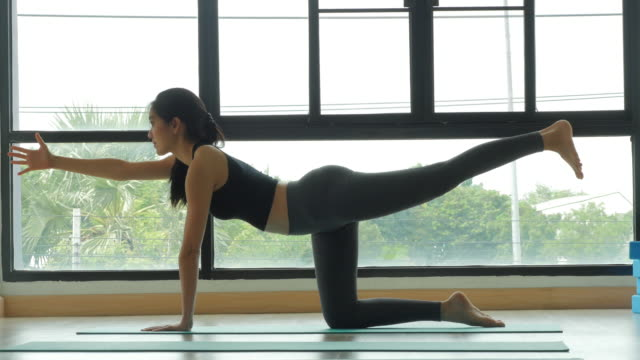 Beautiful young lady does yoga. Side view.