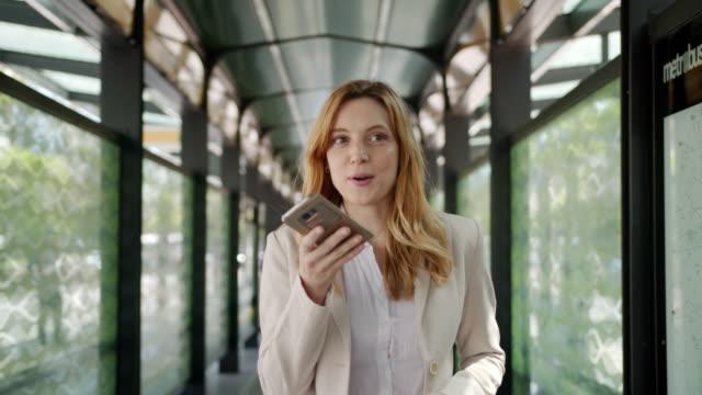 vidéos et rushes de belle jeune femme d'affaires américaine latine marchant à la station de bus utilisant le haut-parleur riant très excité - femme d'affaires