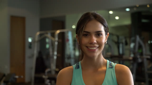 beautiful young latin american personal trainer at the gym facing camera smiling - fitness instructor stock videos & royalty-free footage
