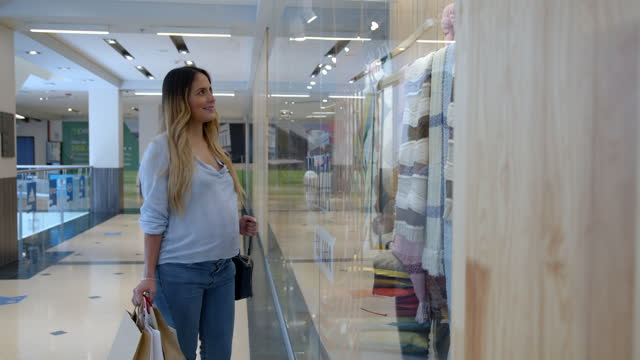 vídeos de stock e filmes b-roll de beautiful young latin american pregnant woman walking around the mall holding paper bags and looking at the window displays - abdómen humano