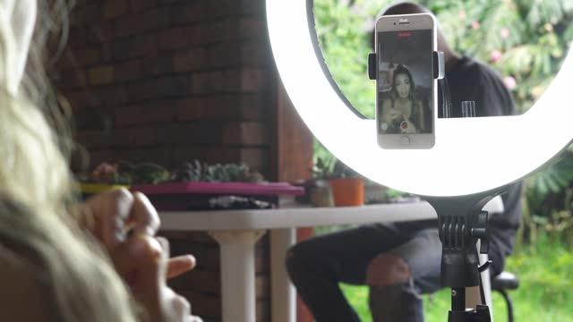 vidéos et rushes de belle jeune latina enseigne son cours d'entraîneur personnel à ses élèves par téléphone portable dans un spectacle en direct tout en utilisant son anneau de lumière et en motivant ses abonnés avec des mots - blog