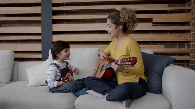 vídeos y material grabado en eventos de stock de hermosa joven mamá tocando la guitarra con su hijo tanto divirtiéndose sonriendo y cantando - guitarra
