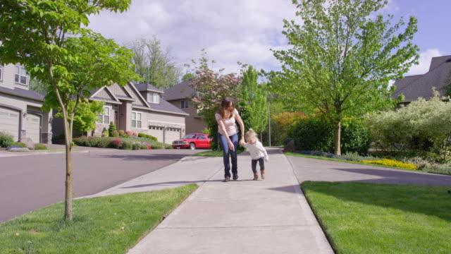 vídeos de stock, filmes e b-roll de linda jovem mãe e filha a passar tempo juntos tocando etiqueta ao ar livre - brincadeira de pegar