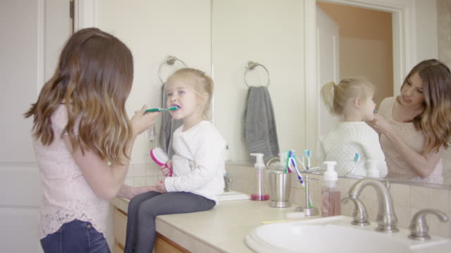 beautiful young mother brushing her young toddler's teeth - brushing stock videos and b-roll footage