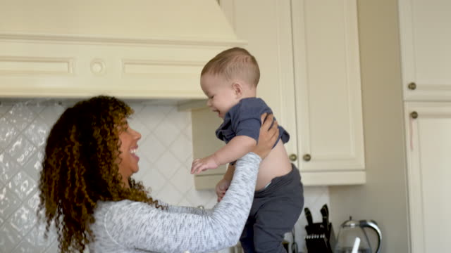 beautiful young mother cooking with her baby - fatcamera baby stock videos and b-roll footage