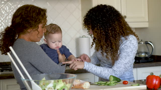 beautiful young mother cooking with her mom and baby - fatcamera baby stock videos and b-roll footage
