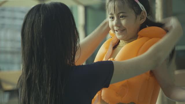 bella giovane madre che aiuta sua figlia a indossare il giubbotto di salvataggio prima di giocare in piscina. - giacca di salvataggio video stock e b–roll