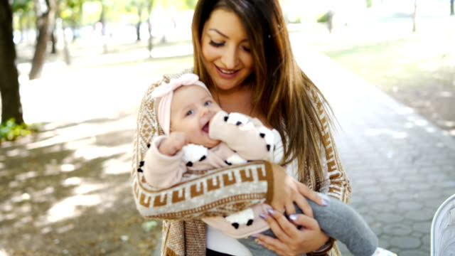 beautiful young mother holding her baby girl - baby clothing stock videos & royalty-free footage