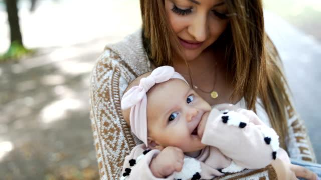 beautiful young mother holding her baby girl - abbigliamento da neonato video stock e b–roll