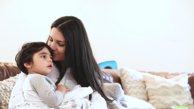 vídeos y material grabado en eventos de stock de hermosa madre joven rocas y consuela a su hijo pequeño mientras está sentado en el sofá en casa - balancearse