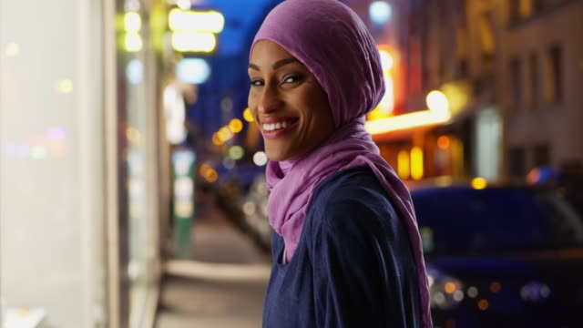 beautiful young muslim woman in urban setting, smiling at camera - modest clothing stock videos & royalty-free footage