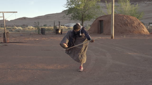 beautiful young navajo girl in monument valley arizona in her yard in front of a traditional hogan performing and wearing a covid-19 mask - navajo culture stock videos & royalty-free footage