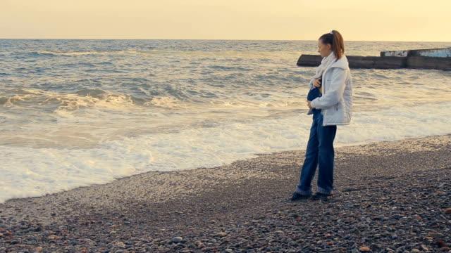 Vacker ung gravid kvinna vilar på stranden vid solnedgången