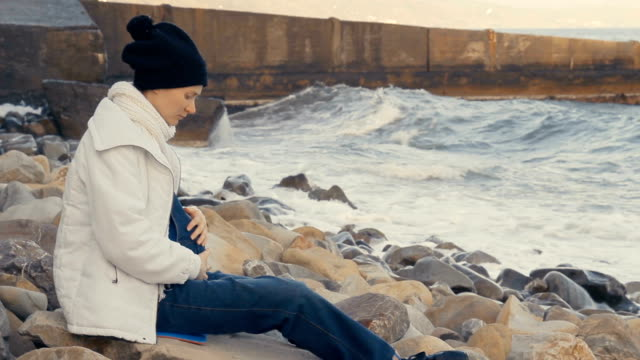 Beautiful young pregnant woman resting on shore of stormy sea