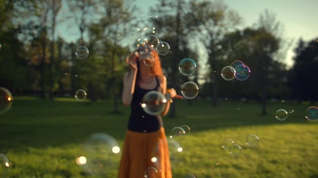 Beautiful young redhair girl blowing soap bubbles outdoors. Sunrise
