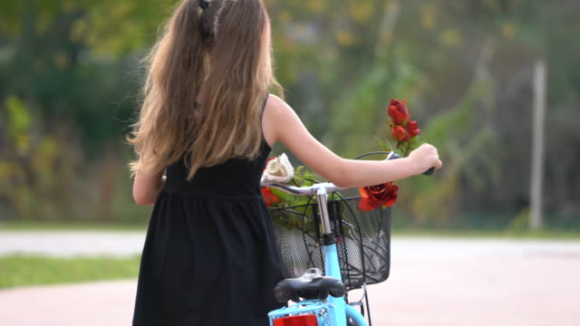 Beautiful young tanager girl riding a bike on a sunny day
