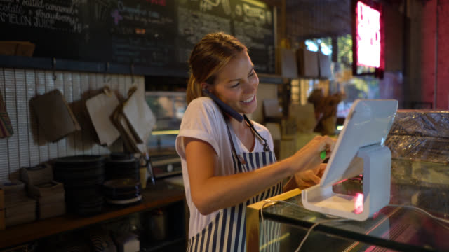 beautiful young waitress registering a delivery on system while talking to customer on phone - ristorante video stock e b–roll