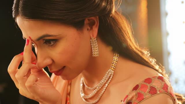 cu beautiful young woman applying bindi and touching diamond necklace during diwali festival / new delhi, delhi, india - bindi stock videos and b-roll footage