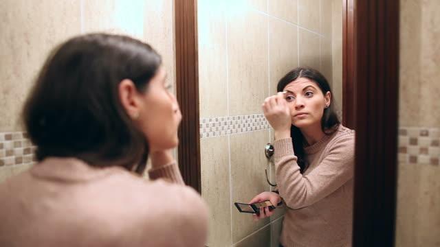 vídeos de stock e filmes b-roll de bela jovem mulher aplicar cosméticos. - casa de banho