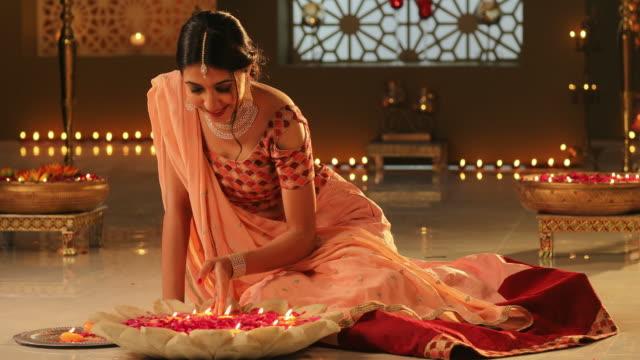 MS Beautiful young woman arranging oil lamps during Diwali festival / New Delhi, Delhi, India
