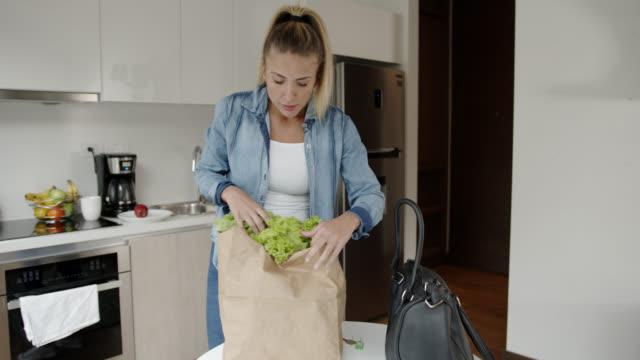 紙袋に新鮮な食料品を持って家に到着美しい若い女性 - 買い物袋点の映像素材/bロール