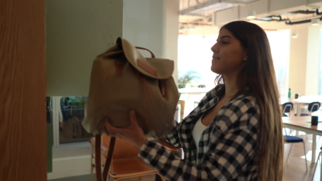 beautiful young woman arriving to the office putting her backpack away in a locker smiling - locker stock videos & royalty-free footage