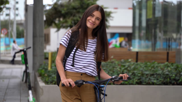 beautiful young woman arriving to the office standing next to her bicycle while smiling at camera - america del sud video stock e b–roll