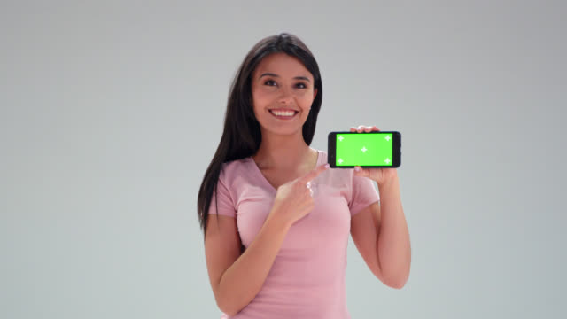 schöne junge frau in einem studio zeigt auf den bildschirm des smartphones lächelnd auf die kamera - chroma-taste, - braunes haar stock-videos und b-roll-filmmaterial