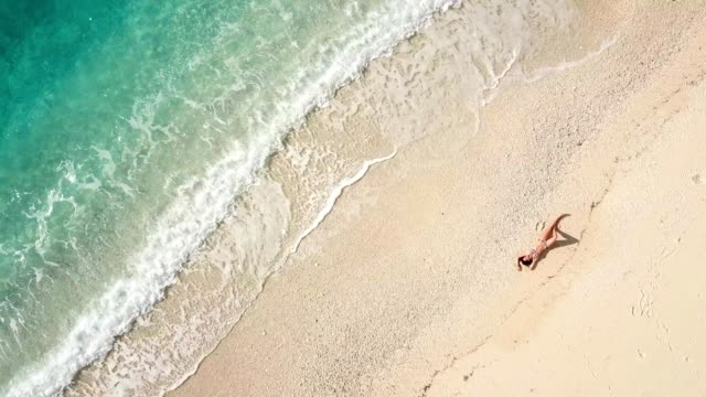 beautiful young woman at the beach, drone view - sunbathing stock videos & royalty-free footage