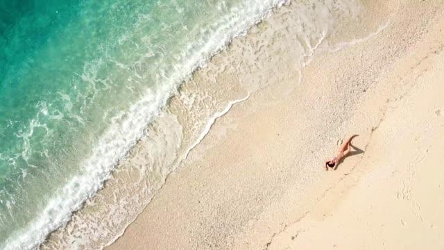 vídeos de stock e filmes b-roll de beautiful young woman at the beach, drone view - apanhar sol