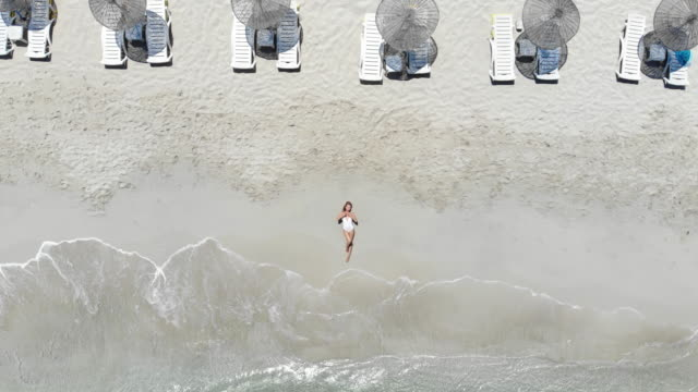 beautiful young woman at the beach, drone view - bikini stock videos & royalty-free footage