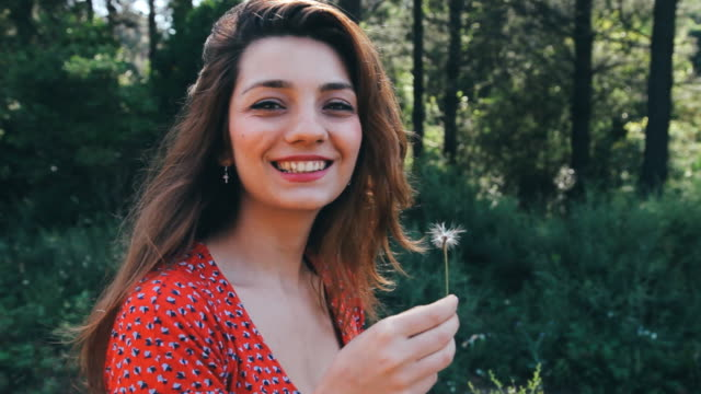 Beautiful young woman blowing a dandelion and smiling