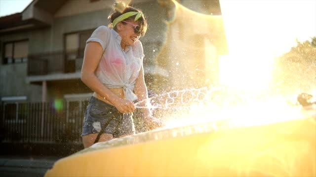 Beautiful young woman car washing in the street