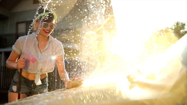 vidéos et rushes de voiture de belle jeune femme lavant dans la rue - pin up