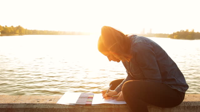 "Beautiful young woman coloring books on the lake shore at sunset - Brief 603439111 ""CreativeContentBrief"""