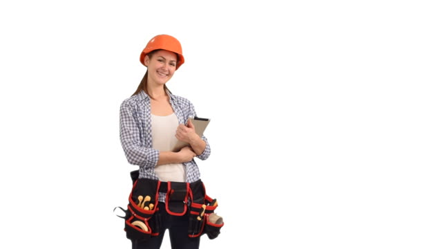 Beautiful young woman construction worker working on tablet