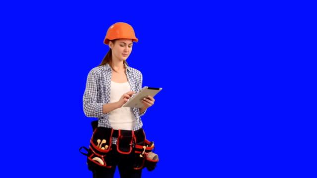 Schöne junge Frau Bauarbeiter arbeiten auf einem tablet arbeitet