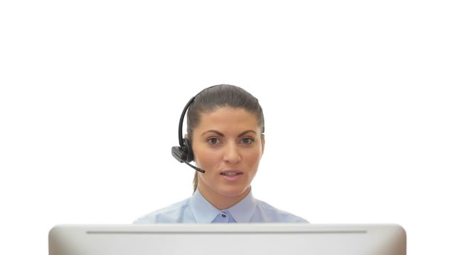 beautiful young woman customer service in front of the computer talking over the headset on white background. - computer monitor white background stock videos & royalty-free footage