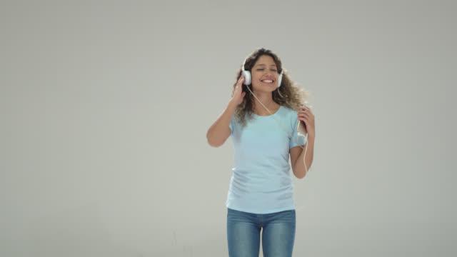 vidéos et rushes de belle jeune femme dansant avec la musique d'écoute fermée d'yeux utilisant le casque et le smartphone - application mobile