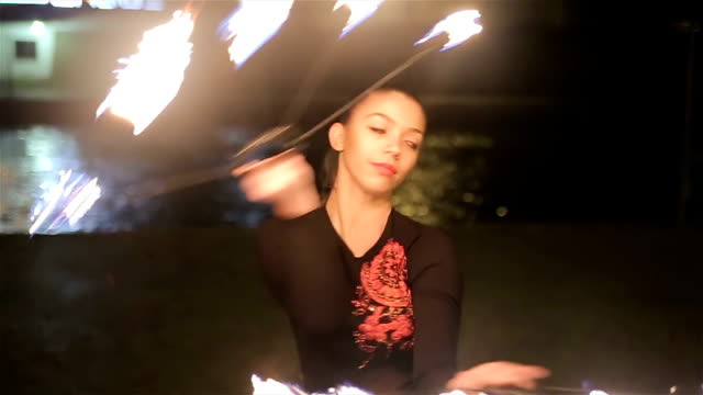 beautiful young woman dancing with fire