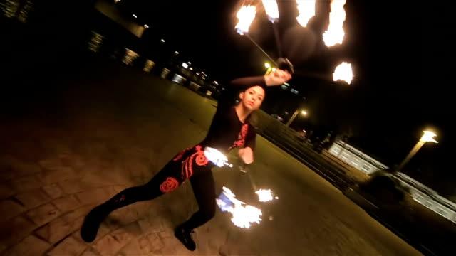 vidéos et rushes de belle jeune femme qui danse avec le feu, feu voir la performance - activité acrobatique