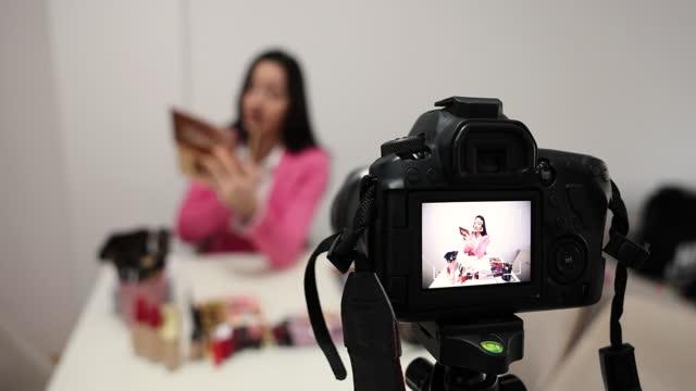 vídeos de stock, filmes e b-roll de linda jovem mulher demonstrando um produto de maquiagem - só uma adolescente menina