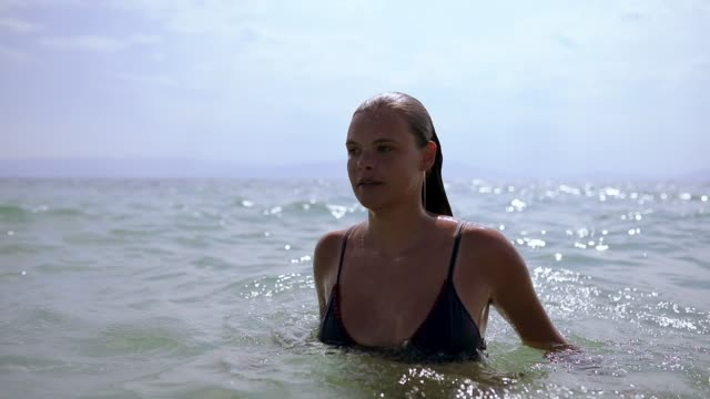 beautiful young woman diving into the sea on summer vacation at greece - wet hair stock videos & royalty-free footage