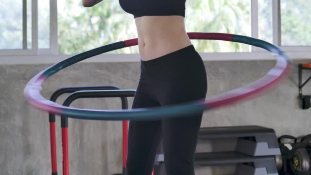 stockvideo's en b-roll-footage met mooie jonge vrouw doet een mooie figuur in de sportschool - fitnessapparatuur