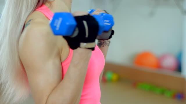 vídeos de stock, filmes e b-roll de bela jovem dando uma bela figura na academia de ginástica - concentração